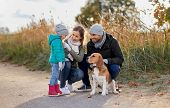 family, pets and people concept - happy mother, father and little daughter with beagle dog outdoors  poster