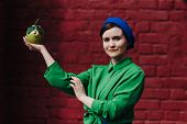 Stylish Young Woman In Blue Beret And Skirt With A Green Shirt Is Standing On The Street On A Urban poster