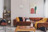 Flowers In Vase On Wooden Coffee Table In Fashionable Living Room Interior With Brown Corner Sofa Wi poster