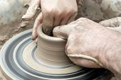 Two Pairs Of Hands Mold Something From Clay On A Potters Wheel poster