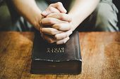 Spirituality And Religion, Hands Folded In Prayer On A Holy Bible In Church Concept For Faith. poster