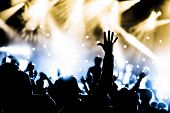 stock photo of adoration  - crowd cheering with hands raised at a live music concert - JPG