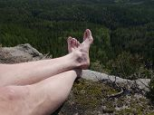 Tired Hikers Legs Without Shoes. Man Hiker Legs Climbed At Mountain Peak Rock poster