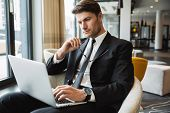Portrait of serious young businessman wearing formal black suit sitting on armchair with laptop comp poster
