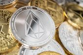 Eos Cryptocurrency Coin With Big Eos Symbol In The Centre Of It. Eos Physical Coin On The Stack Of O poster