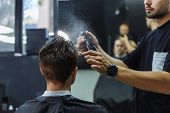 Attractive Male Is Getting A Modern Haircut In Barber Shop. Barber Wets Hair By Spray And Combs Them poster