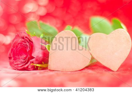 Two chocolate hearts with rose in lovely background