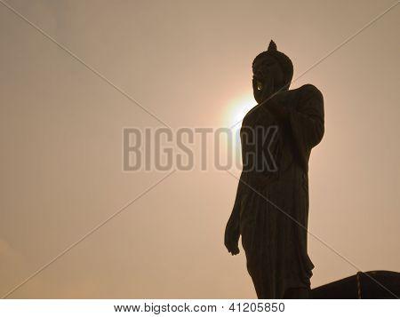 Silhouette Walking Buddha Image In Vitarka Mudra Posture