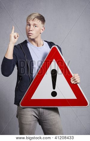 Other danger ahead warning road sign hold by serious man with finger pointing up to draw attention, isolated on grey background.