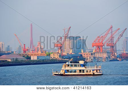 Boat in Huangpu River with Shanghai urban architecture and cargo crane
