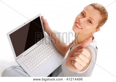 Young girl with a laptop sitting on the floor, showing ok
