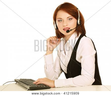 A smiling young customer service girl with a headset at her workplace, closeup, isolated on white background