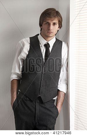 Young serious businessman near the window