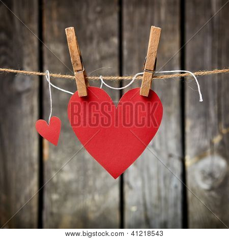 Two lovely red hearts - big and small hanging on the clothesline. On old wood background.