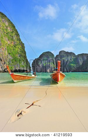 Scenic green islands of Thailand coast. Emerald sea and fine white sand. In sand approached by two tourist boats, decorated with colorful silk scarves and wreaths