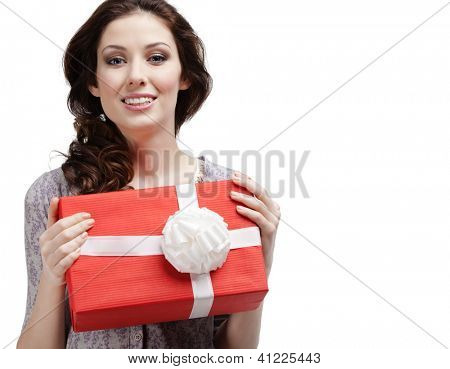 Young woman hands a gift wrapped in red paper with white bow, isolated on white