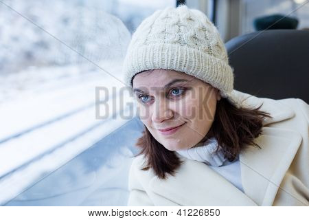 Young Woman Traveling By Train And Looking Out The Window