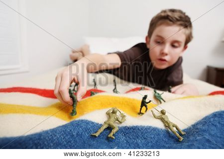 Young boy laying on his bed playing with toy soldiers (focus on toy soldiers in foreground)