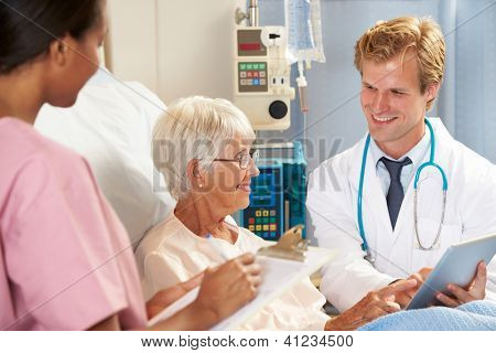 Doctor Using Digital Tablet In Consultation With Senior Female Patient In Bed