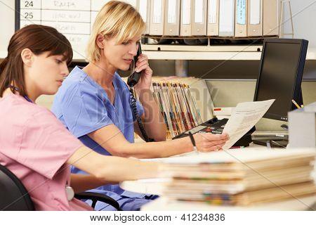 Two Nurses Working At Nurses Station