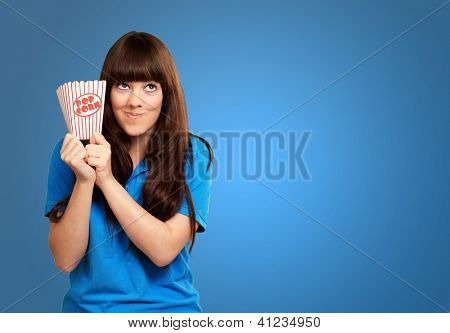 girl holding empty popcorn packet isolated on blue background