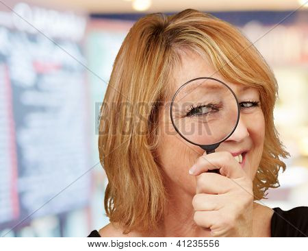 Woman looking through magnifying glass, indoor