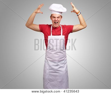Angry Young Man Raising His Hand On Gray Background