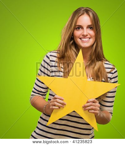 Young Woman Holding Yellow Star against a green background