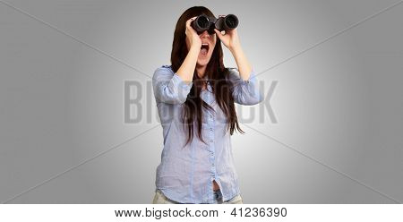 Portrait Of A Young Woman Looking Through Binoculars On Gray Background