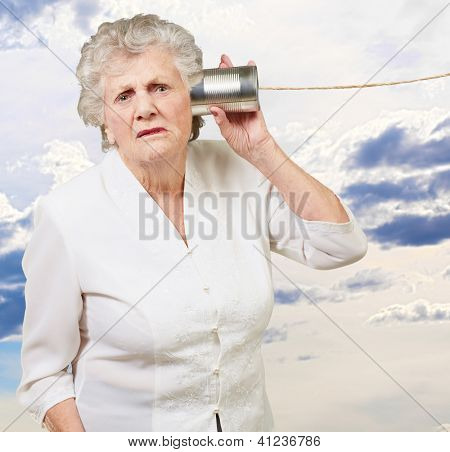 Portrait of a senior woman hearing with metal tin, outdoor