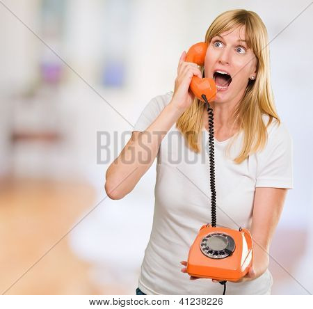 shocked woman talking on telephone against an abstract background, indoor