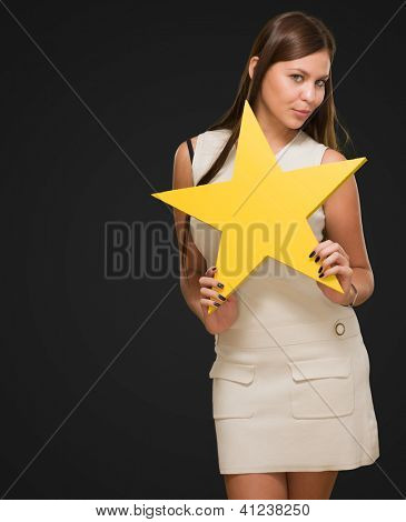 Portrait Of Young Woman Holding Yellow Star against a black background