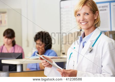 Female Doctor Using Digital Tablet At Nurses Station