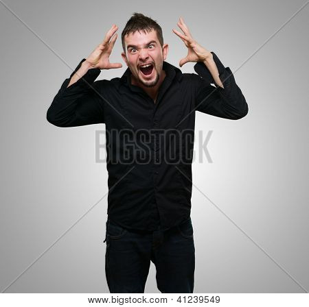 Portrait Of Frustrated Man against a grey background