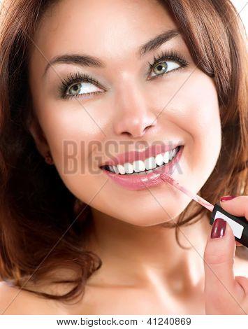 Beauty Girl Applying Lipgloss. Makeup. Beautiful Woman's Face. Apply Make-up. Healthy Smile. White Teeth.