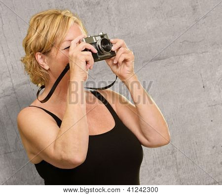 Mature Woman Looking Through Camera On Wall