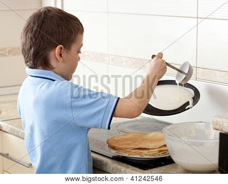 Child bakes pancakes in the kitchen. Boy cooking breakfast