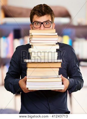 Young Man Holding Pile Of Book, Indoors