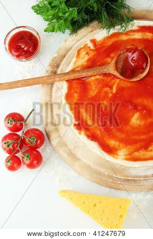 Pizza dough with tomato sauce on wooden board isolated on white