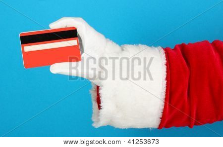 Santa Claus hand holding red credit card on blue background