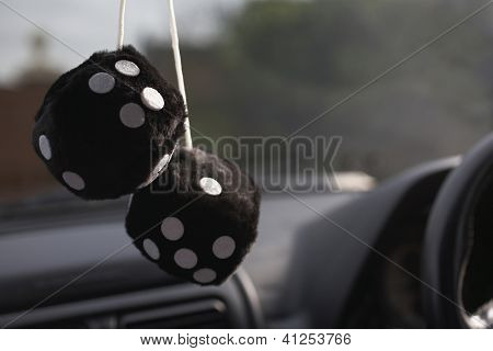 Pair of fuzzy dice hanging in a car`s windshield