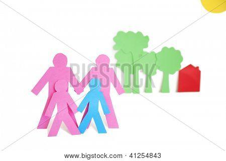 Corte de papel salidas representando a una familia con árboles y casas sobre fondo blanco