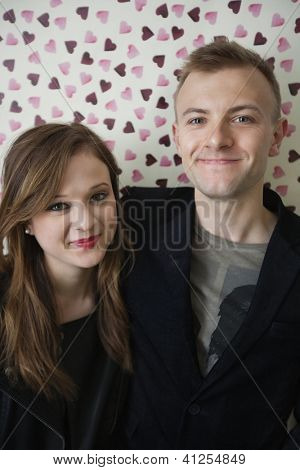 Portrait of beautiful young couple smiling over heart shaped wallpaper