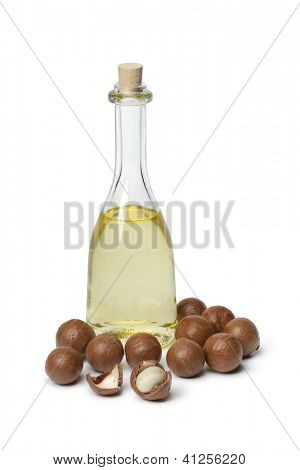 Bottle with Macadamia oil and nuts on white background