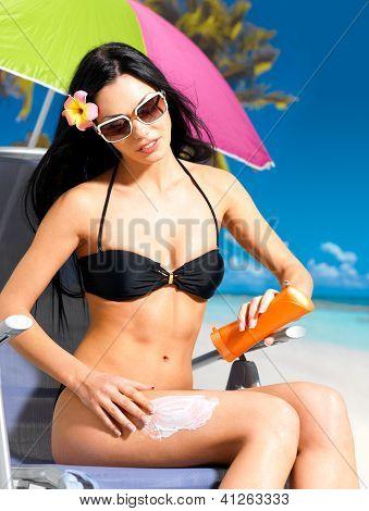 Woman In Bikini Applying Sun Block Cream On Body