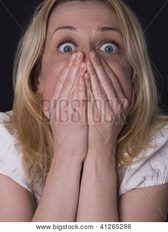 blonde woman covering her mouth with her hands