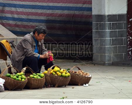 Vendor Cleaning Oranges With No Customers In Sight