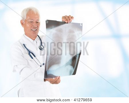 Asian senior doctor checking on x-ray image inside hospital room