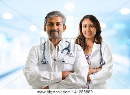 Indian doctors or medical team crossed arms standing, hospital background