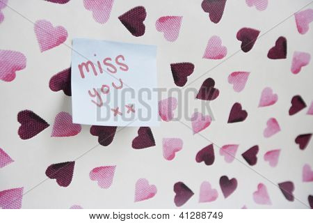 Close-up of sticky note with a message over heart shaped wall